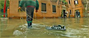 Acqua Alta Venise: Petit Vénitien profitant de l'occasion pour jouer avec son bateau de police devant la caserne des Carabinieri, Campo San Zaccaria, dans le Sestier du Castello à Venise.