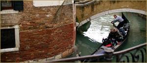 Virage serré en gondole sous le pont privé de Ca' Venier, dans le Sestier du Castello à Venise.