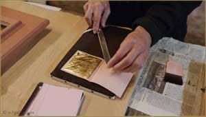 L'extraction par le maître doreur des feuilles d'or du carnet les contenant.
