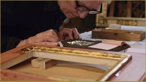 La préparation de la feuille d'or par le maître doreur Gennaro Stolfi, ici il souffle légèrement sur la feuille pour qu'elle adhère au support de velours sur lequel il coupera chaque feuille à la mesure nécessaire.