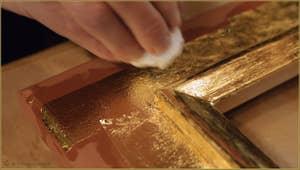 La feuille d'or est ensuite tamponnée avec un coton pour éliminer au maximum la colle sur laquelle elle repose et la faire mieux adhérer au cadre.