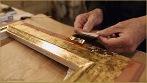 La pose des feuilles d'or sur le cadre par le Maître doreur Gennaro Stolfi.