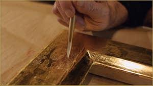 Le maître doreur Gennaro Stolfi en train de créer un effet décoratif supplémentaire en piquetant certaines parties des motifs avec une pointe d'agate. Dans son atelier, fondamenta Sant'Andrea à Venise.