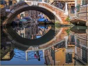 L'œil du pont Riello dans les reflets du Rio San Daniele, dans le Castello à Venise.