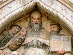 Bas relief représentant Saint-Augustin et ses disciples sur le portail d'entrée du cloître Santo Stefano à Venise