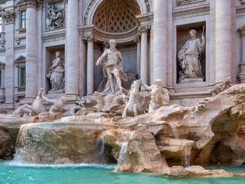 La fontaine de Trevi à Rome en Italie avec les statues de l'Abondance et de la Santé de chaque côté de Neptune le roi de l'océan sur son char tiré par les chevaux marins ailés accompagnés des Tritons