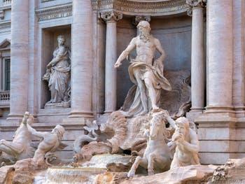 La fontaine de Trevi à Rome en Italie avec la statue de l'Abondance et Neptune, roi de l'océan perché sur son char en forme de coquille tiré par les chevaux marins ailés et les Tritons