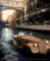 Livio de Marchi sous le pont des Soupirs à Venise au volant d'une Jaguar 1934 en bois sculpté