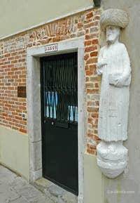 """Ci-dessus, la première statue qui se trouve sur le Campo dei Mori, au numéro 3384B. Cette statue, à l'origine sans aucun turban, reste un mystère au niveau de son interprétation. Si elle est bien la statue de l'un des frères Mastelli, qu'en est il de l'étole, ressemblant à celle d'un prêtre, posée sur la veste de l'homme ? L'homme tient de plus une partie de cette étole avec l'une de ses mains, comme pour mieux en indiquer sa fonction religieuse. On serait donc en face d'un prêtre chrétien, si cette hypothèse était vérifiée, bien loin d'un """"Arabe"""", comme le turban rajouté deux siècles plus tard voudrait le faire croire"""