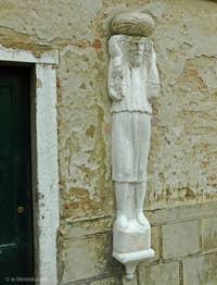 Ci-dessus, la seconde statue sur le Campo dei Mori, au numéro 3385. C'est un homme aux cheveux longs qui porte à deux mains un fardeau sur ses épaules